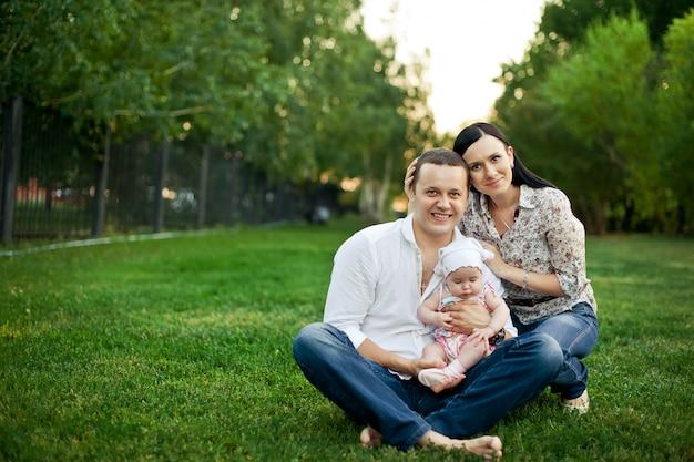 Glückliche junge familie, die zusammen zeit draußen in der grünen natur verbringt Premium Fotos