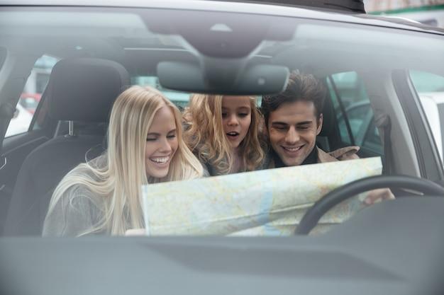 Glückliche junge familie im auto, das karte hält. Kostenlose Fotos