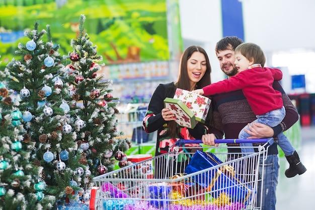 Glückliche junge familie im supermarkt wählt geschenke für das neue jahr. Premium Fotos
