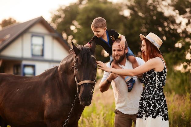Glückliche junge familie mit einem kleinen sohn steht mit einem pferd vor einem kleinen landhaus Kostenlose Fotos