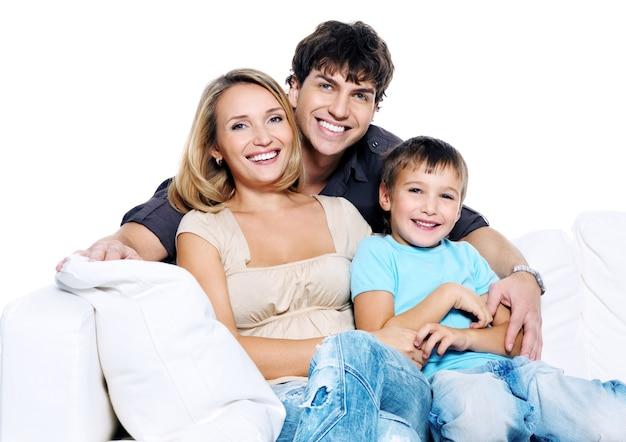 Glückliche junge familie mit kind, das auf weißem sofa lokalisiert lokalisiert Kostenlose Fotos