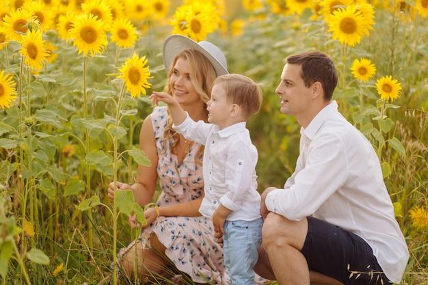 Glückliche junge familie, mutter, vater und sohn, lächeln, halten und umarmen sich im sonnenblumenfeld Kostenlose Fotos