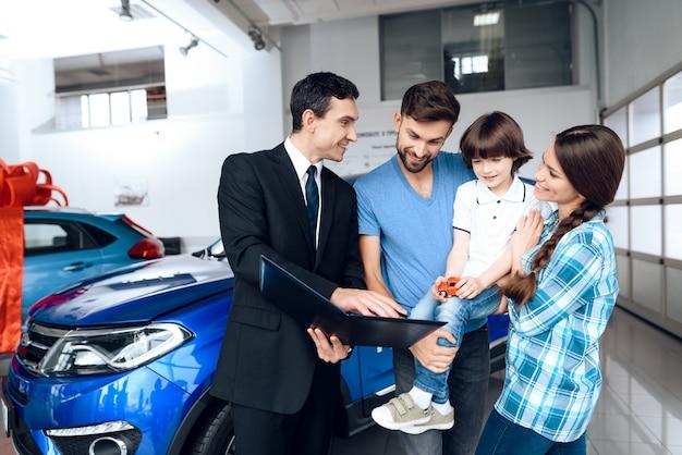 Glückliche junge familie wählen ein neues auto. Premium Fotos
