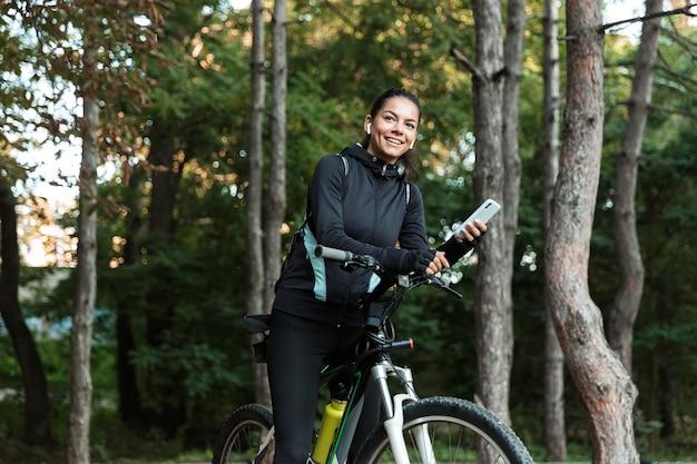 Glückliche junge fitnessfrau, die auf einem fahrrad am park reitet, musik mit kopfhörern hörend, handy hält Premium Fotos