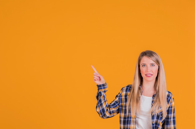 Glückliche junge frau, die aufwärts seinen finger gegen einen orange hintergrund zeigt Kostenlose Fotos