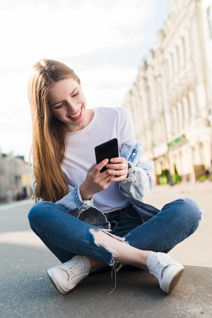 Glückliche junge frau, die den smartphone sitzt auf straße verwendet Kostenlose Fotos