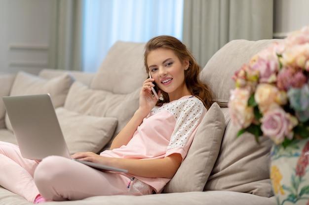 Glückliche junge frau, die durch smartphone, das am computer arbeitet, anruft. attraktive frau mit handy und laptop. Kostenlose Fotos