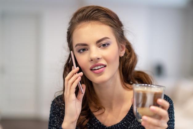 Glückliche junge frau, die durch smartphone zu hause spricht. attraktive frau, die drinnen telefonisch anruft. Kostenlose Fotos
