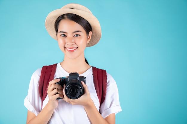 Glückliche junge frau, die eine kamera hält Premium Fotos