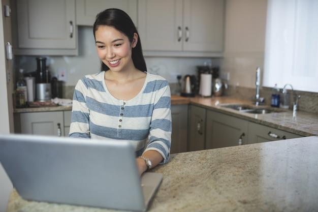 Glückliche junge frau, die einen laptop in der küche verwendet Premium Fotos