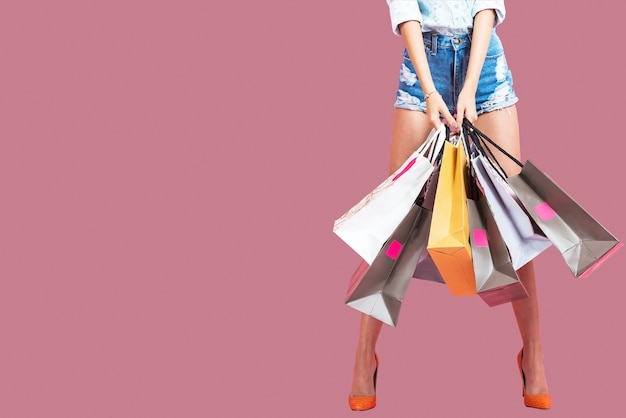 Glückliche junge frau, die einkaufstaschen auf einem rosa hintergrund hält Premium Fotos