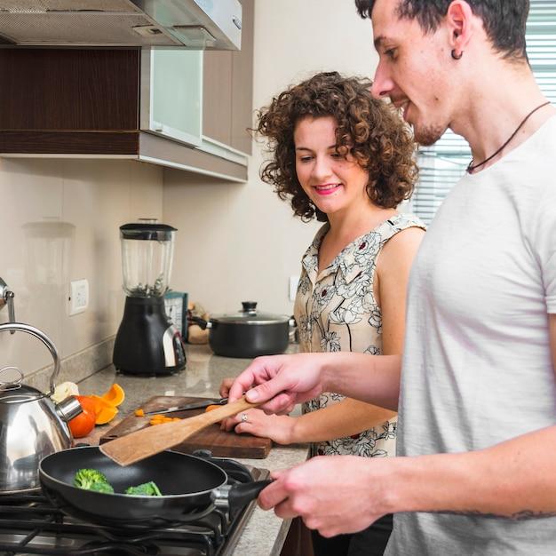 Glückliche junge frau, die ihren ehemann kocht brokkoli in der bratpfanne betrachtet Kostenlose Fotos