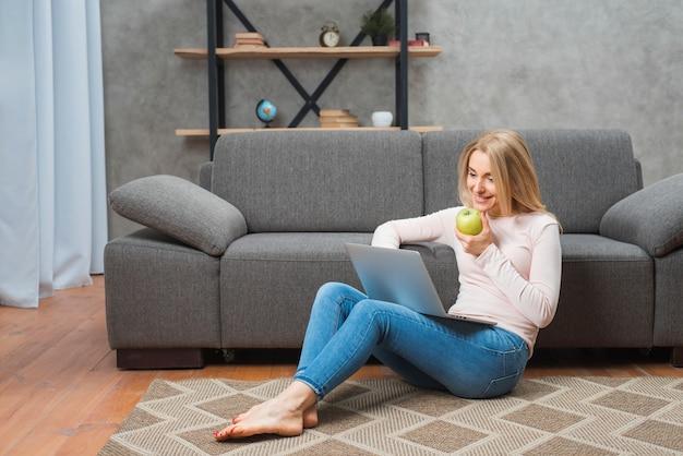 Glückliche junge frau, die in der hand auf dem teppich hält grünen apfel unter verwendung des laptops sitzt Kostenlose Fotos