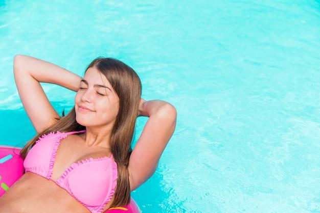 Glückliche junge frau, die in wasser schwimmt Kostenlose Fotos