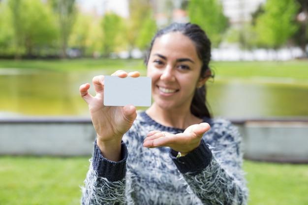 Glückliche junge frau, die leere visitenkarte im stadtpark zeigt Kostenlose Fotos
