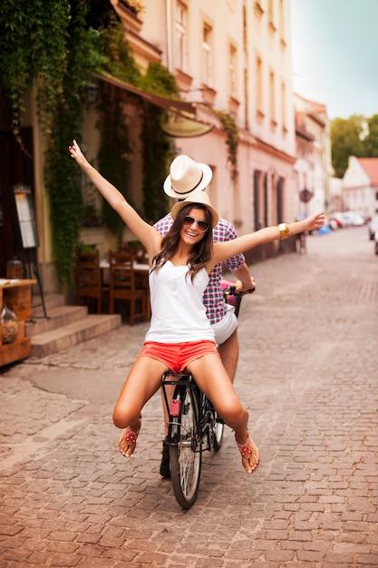 Glückliche junge frau, die mit ihrem freund auf fahrrad reitet Kostenlose Fotos
