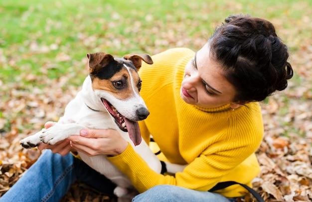 Glückliche junge frau, die mit ihrem hund spielt Kostenlose Fotos