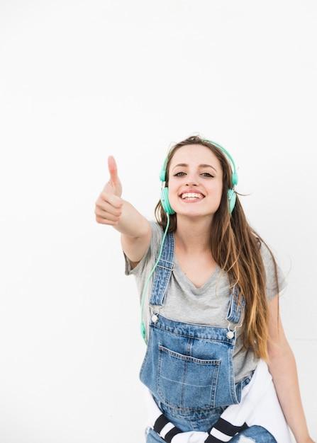 Glückliche junge frau, die thumbup zeichen gegen weißen hintergrund zeigt Kostenlose Fotos