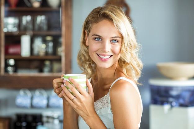 Glückliche junge frau, die zu hause kaffeetasse hält Premium Fotos