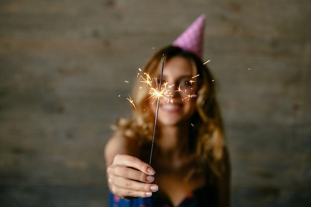 Glückliche junge frau hält das fokussierte bengal-licht und feiert den feiertag Kostenlose Fotos