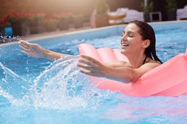 Glückliche junge frau im bikini mit aufblasbarer gummimatratze, spielend und gute zeit am wasserbecken während des heißen sommertages nass Kostenlose Fotos