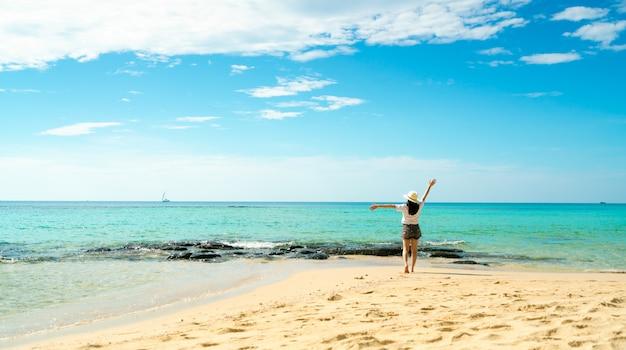 Glückliche junge frau in den weißen hemden und in den kurzen hosen, die am sandstrand gehen. entspannen und urlaub am tropischen paradiesstrand genießen. mädchen in den sommerferien. sommergefühl. glücklicher tag. Premium Fotos