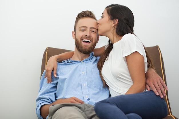 Glückliche junge frau küsst ihren mann leidenschaftlich