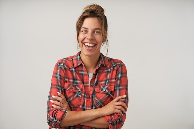 Glückliche junge frau mit brötchenfrisur, die auf weiß aufwirft, freudig lächelnd mit gekreuzten händen auf ihrer brust, positives gefühlskonzept Kostenlose Fotos