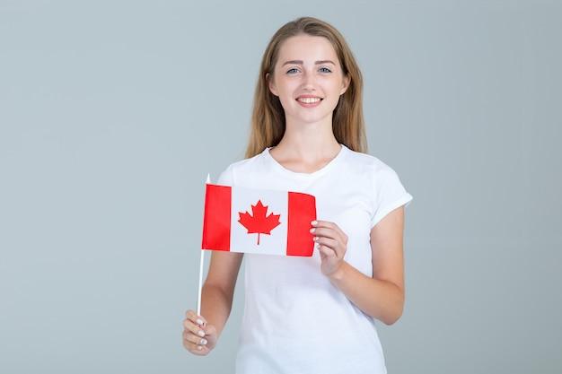 Glückliche junge frau mit der flagge von kanada auf grau Premium Fotos