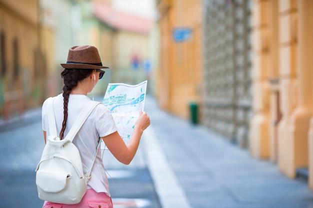 Glückliche junge frau mit einem stadtplan in der stadt. touristische frau der reise mit karte in prag draußen während der feiertage in europa. Premium Fotos