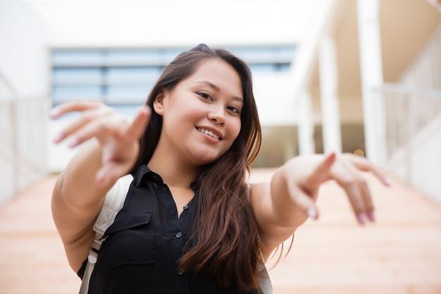 Glückliche junge frau mit rucksack zeigend auf kamera Kostenlose Fotos