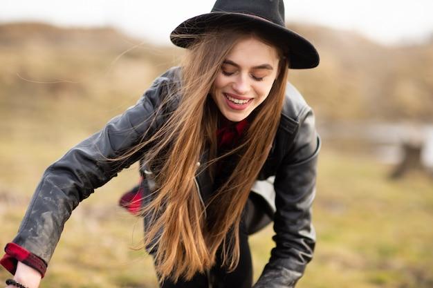 Glückliche junge frau mit schwarzem hut Premium Fotos
