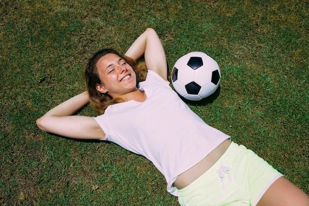 Glückliche junge frau nahe ball auf gras Kostenlose Fotos
