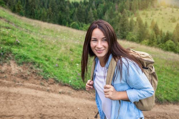 Glückliche junge frau tourist geht mit rucksack im hochland. aktives lifestyle-konzept Premium Fotos