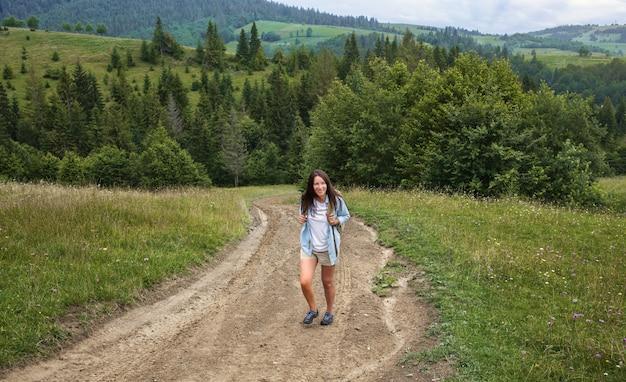 Glückliche junge frau tourist geht mit rucksack im hochland. aktives und gesundes lifestyle-konzept Premium Fotos