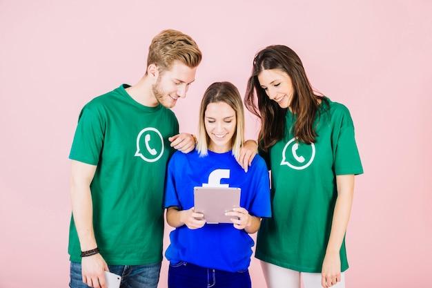 Glückliche junge freunde, die digitale tablette betrachten Kostenlose Fotos