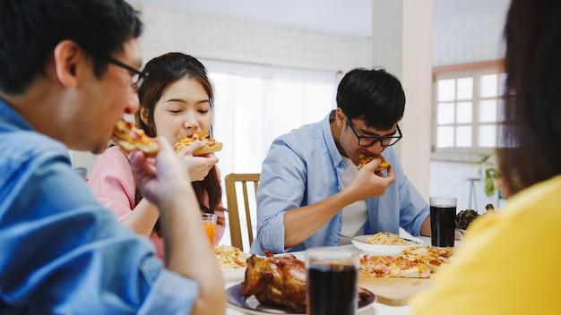 Glückliche junge freunde gruppe, die zu hause zu mittag isst. asia familienfeier, die pizza essen isst und lachend das essen genießt, während sie am esstisch zusammen im haus sitzt. festurlaub und zusammengehörigkeit. Kostenlose Fotos