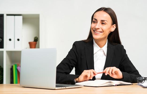 Glückliche junge geschäftsfrau, die hinter dem schreibtisch mit buch sitzt; stift und laptop Kostenlose Fotos