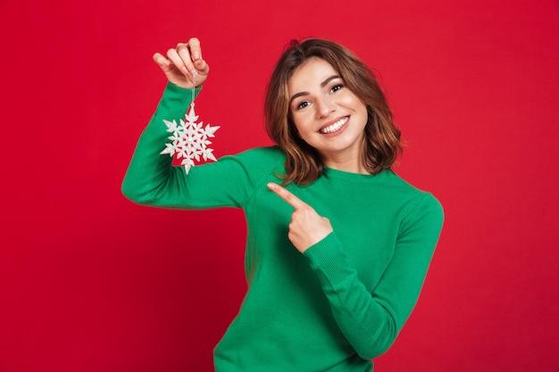 Glückliche junge hübsche frau, die das schneeflockenzeigen hält. Kostenlose Fotos