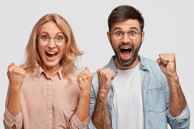 Glückliche junge kollegen oder geschäftspartner freuen sich über den erfolg, ballen die fäuste und rufen mit triumph aus Kostenlose Fotos