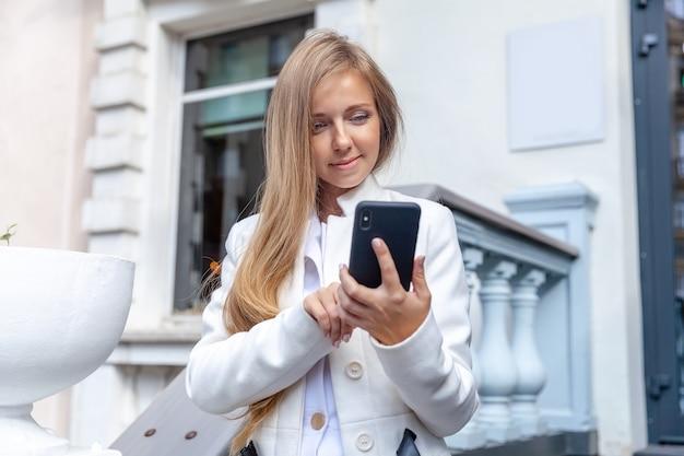 Glückliche junge lächelnde frau, die einen smartphone im freien auf der weinleseartleiter verwendet Premium Fotos