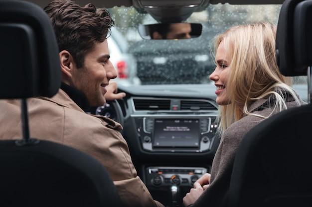 Glückliche junge liebevolle paare im auto, das einander betrachtet. Kostenlose Fotos