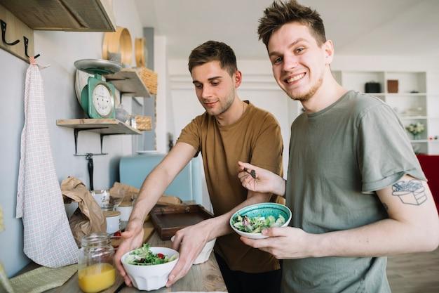 Glückliche junge männer, die salat und fruchtsaft in der küche essen Kostenlose Fotos