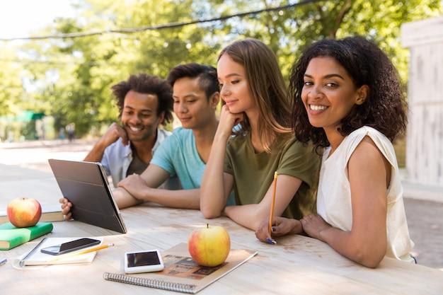 Glückliche junge multiethnische freunde studenten im freien mit tablette Kostenlose Fotos