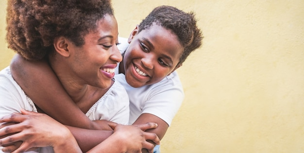 Glückliche junge mutter, die spaß mit ihrem kind hat - sohn, der seine mutter im freien umarmt - familienverbindung, mutterschaft, liebe und zartes momentkonzept - fokus auf jungengesicht Premium Fotos