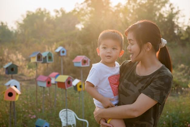 Glückliche junge mutter, die spaß mit ihrem kleinen babysohn im park an einem sonnigen sommertag spielt und hat Kostenlose Fotos