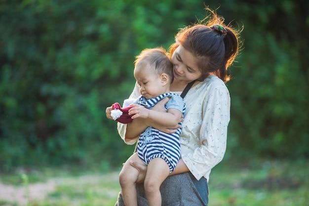 Glückliche junge mutter, die spaß mit ihrem kleinen babysohn spielt und hat Premium Fotos