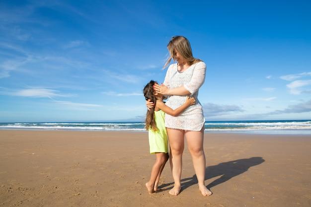 Glückliche junge mutter und niedliches schwarzhaariges mädchen, das beim stehen am ozeanstrand umarmt Kostenlose Fotos
