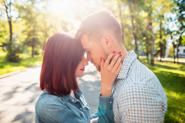 Glückliche junge paare am park, der am hellen sonnigen tag steht und lacht Kostenlose Fotos