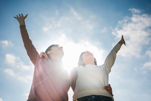 Glückliche junge paare, die im himmel schauen Kostenlose Fotos